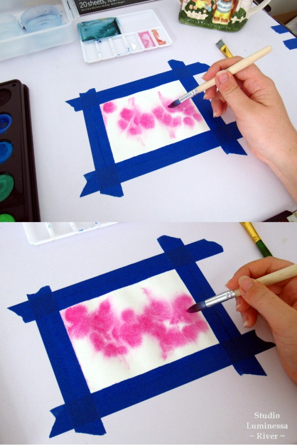 Dropping pink watercolor paint onto wet paper for a diffuse, wet-on-wet look. For the Watercolor Galaxy Tutorial