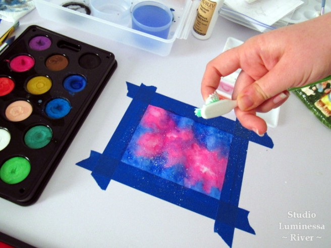 Splattering paint on the watercolor galaxy to make stars.